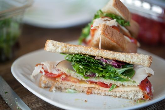 Simple turkey sandwich on honey wheat bread with lettuce and tomato.