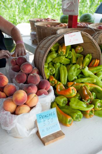 Fresh produce for sale at a farm stand along with some peppers and peaches.  Shallow depth of field.