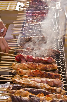 Street fair tend of skewered meat with smoke