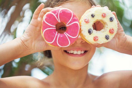 Cute kid girl eating sweet donuts