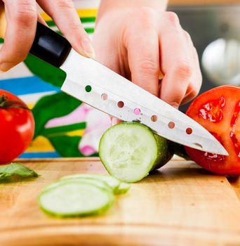 Woman's hands cutting cucumber