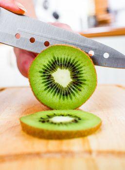 Woman's hands cutting kiwi