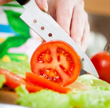 Woman's hands cutting tomato
