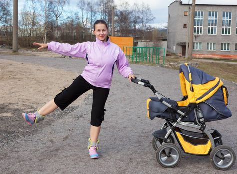 a young mother with a toddler combines walk in a stroller fitness