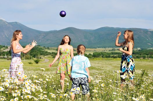 boy and teen girls playing a ball in field