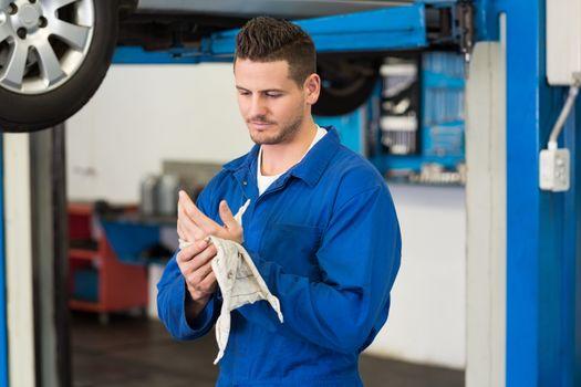 Mechanic wiping hands with rag