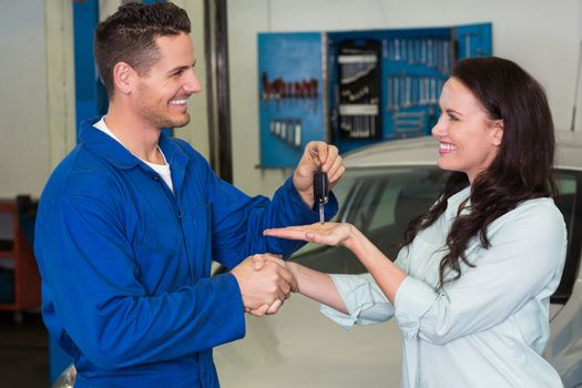 Mechanic giving keys to satisfied customer