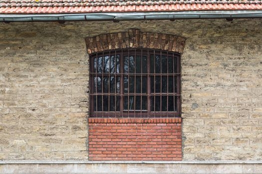 Front view of old window of stone building with gratings.