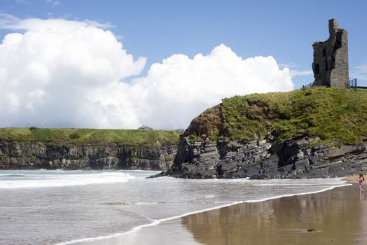 young child on the beach with cliffs and castle on ballybunion beach county kerry ireland