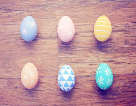 Top view of colorful easter eggs on wooden background with retro filter effect