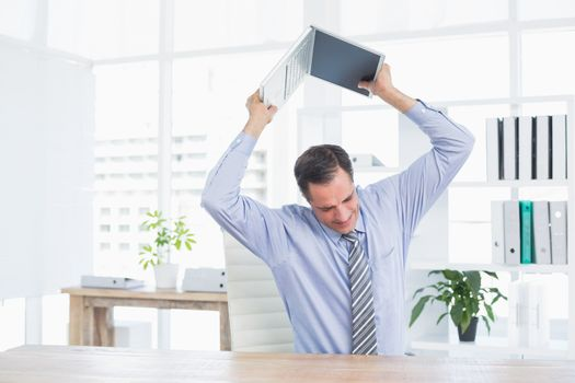 Irritated businessman trying to broke his laptop