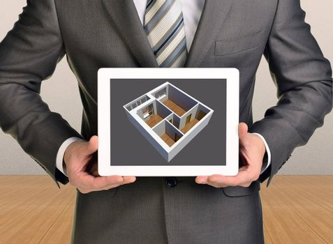 Three-dimensional model of house in tablet screen. Man holding tablet. Wooden floor and gray wall in background