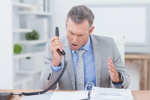 Irritated businessman answering phone