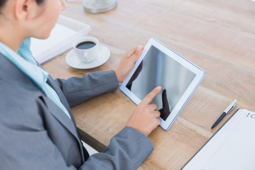 Concentrating businesswoman using a tablet