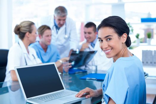 Beautiful smiling doctor typing on keyboard with her team behind in medical office