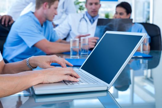 Doctor typing on keyboard with her team behind in medical office