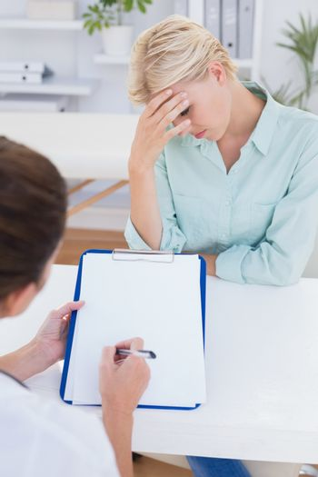 Patient with head ache ache speaking with her doctor