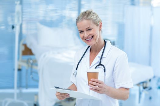 Beautiful smiling doctor holding clipboard and goblet