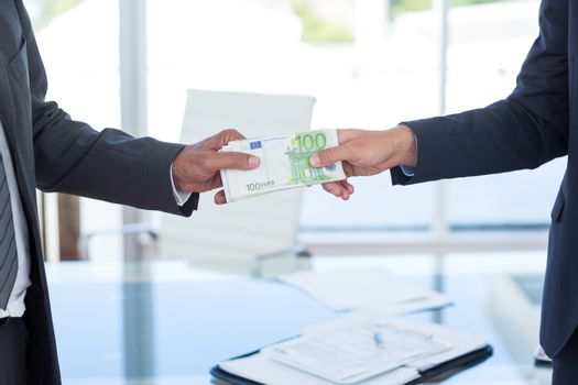 Businessmen shaking hands and exchanging money in an office