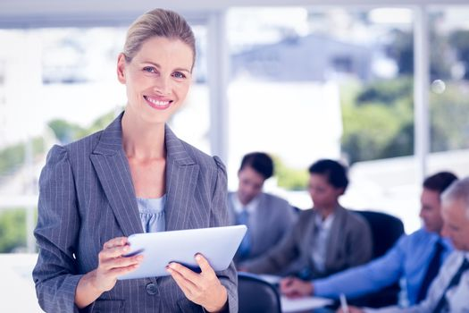 Businesswoman holding tablet and looking at camera