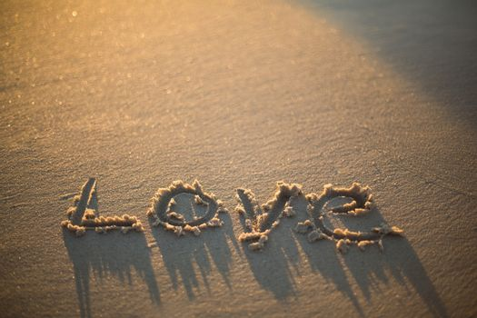 love written on the beach at the sunset
