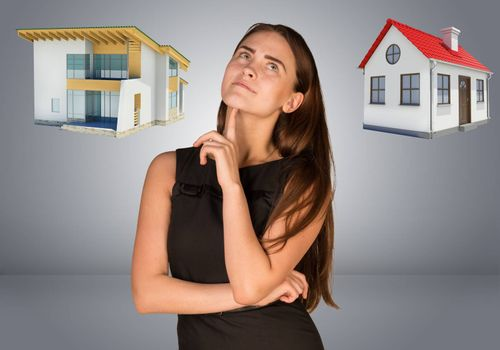 Business woman thinking over house and cottage. Gray gradient background