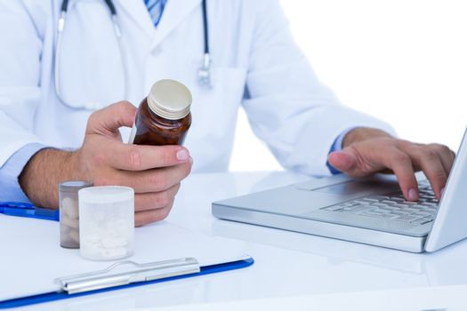 A doctor holding a medecine while typing on a laptop