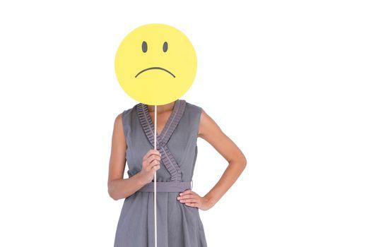 Businesswoman holding sad smiley face