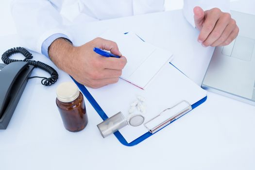 Doctor writing down on a notebook