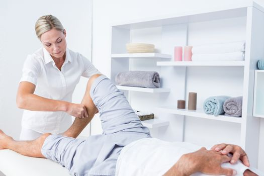 Physiotherapist doing calf massage to her patient