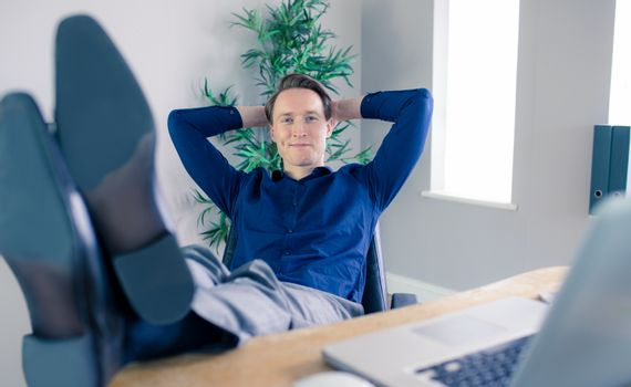 Smiling businessman relaxing in a swivel chair