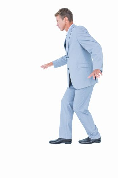 Unsmiling businessman in suit walking