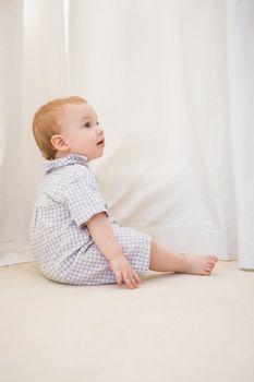 Cute baby boy sitting on floor