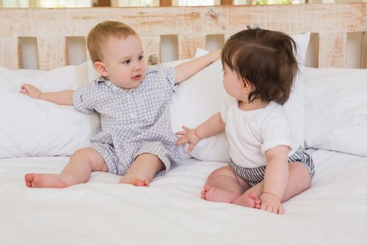 Very beautiful cute babies boy and girl at home in bedroom