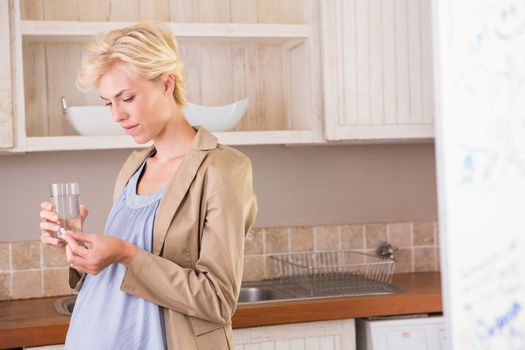 Portrait of a blonde pregnancy taking a vitamin