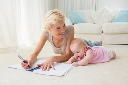 Smiling blonde mother with her baby girl writting on a copybook