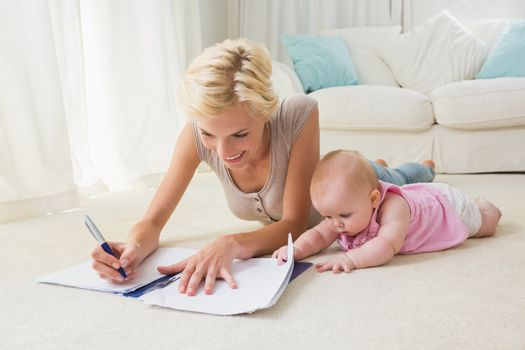 Happy blonde mother with her baby girl writting on a copybook