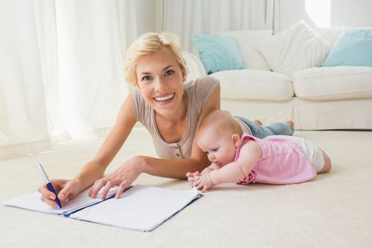 Portrait smiling mother with her baby girl writting on a copybook