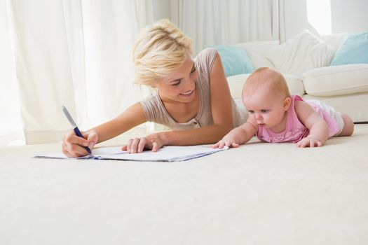 Smiling mother with her baby girl writting on a copybook