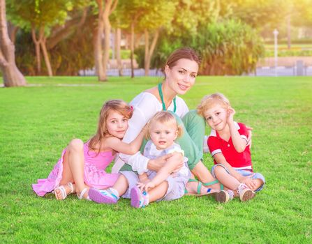 Happy mother with cute little babies sitting on fresh green grass field, having fun outdoors, enjoying parenthood, happiness and love concept