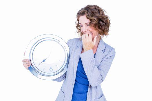 An anxious businesswoman holding clock