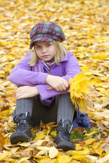 little girl sitting on leaves in the park