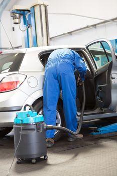 Mechanic vacuuming the car interior