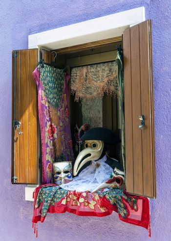 Traditional Venetian carnival accessories at opened window display in Burano island