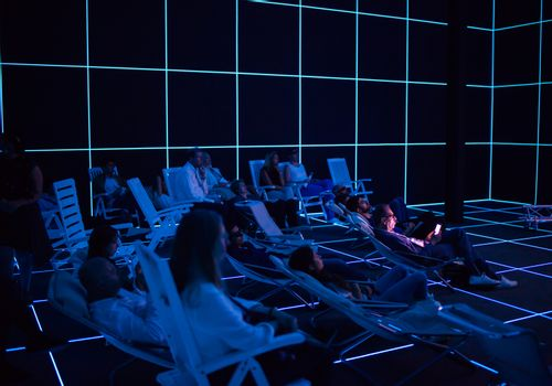 """VENICE, ITALY - MAY 06: People looking """"Factory of the Sun"""" video installation by Hito Steyerl at German pavilion during the 56th Venice Biennale on May 06, 2015"""