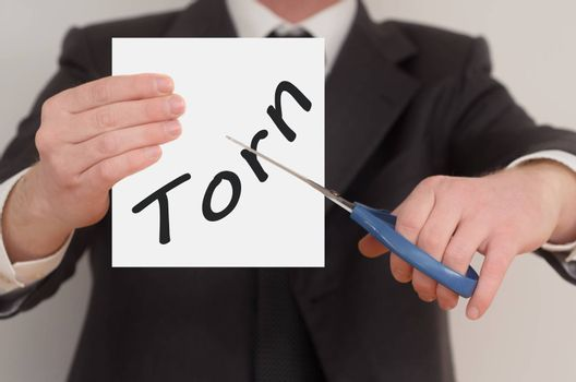 Torn, man in suit cutting text on paper with scissors