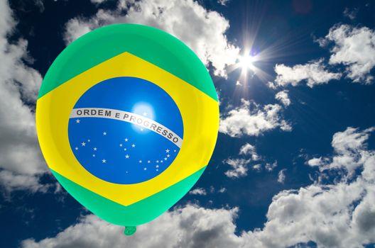 balloon in colors of brazil flag flying on blue sky