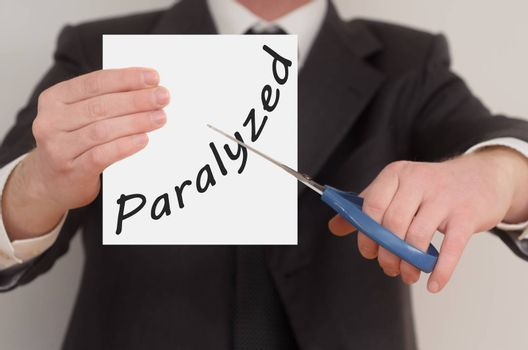 Paralyzed, man in suit cutting text on paper with scissors