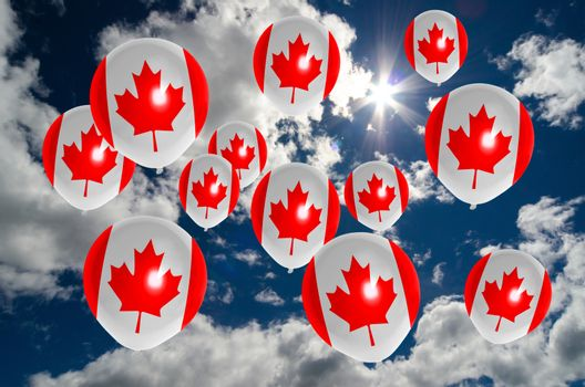 many ballons in colors of canada flag flying on sky