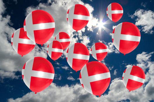 many ballons in colors of denmark flag flying on sky